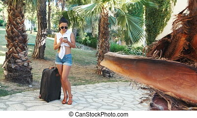 young brunette woman in shorts, sunglasses and heels with...