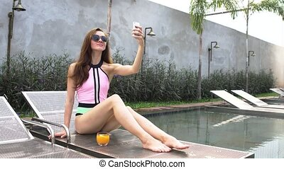 Beautiful girl taking selfie and laughing at the swimming...