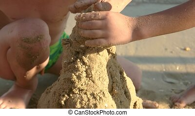 Hands of child, wet sand.