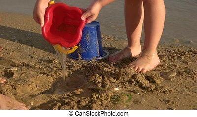 Children playing on the seashore. Leg of kid stomping mud....