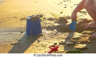 Child playing on the shore. Kid digging pit in sand. Play...