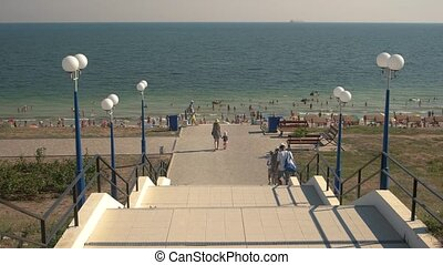 Stairs leading to the sea. People going to the beach. Best...