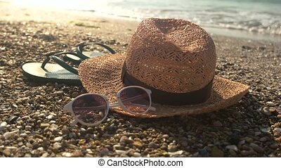 Flip flops near the sea. - Hat with sunglasses on shore....