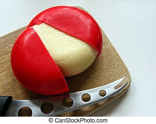Red ball of cheese - A red ball of cheese on a wooden...