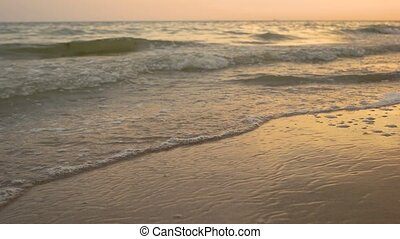 Sandy seashore and waves. Water and sunset sky. Escape from...
