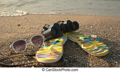 Flip flops and binoculars. Sunglasses on seashore. Explore...