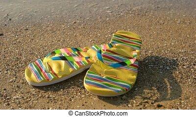 Flip flops on sand background. Footwear on shore. Summer at...
