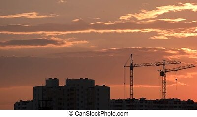 Cranes and buildings, sunset background. Clouds moving over...