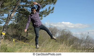 A man wearing a hat and a beard walks the slackline during...