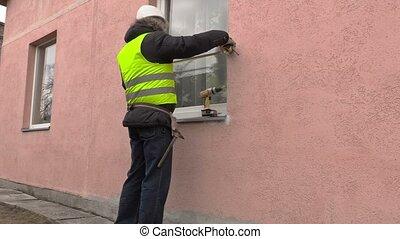 Builder using measure tape near window