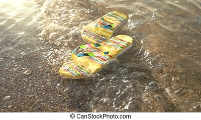 Pair of floating flip flops. Small waves and sunlight. Step...