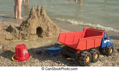 Toys and sandcastle. Toys on seashore. Build your own...