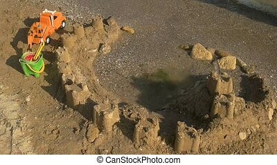Sandcastle and toy car. Toys, sand and water. Sand castle...