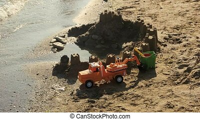Toy car and sandcastle. Toys on the shore. True pearl of...