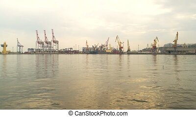 Port and cranes. Water, sky and industrial equipment. Import...