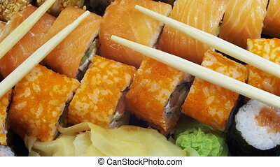 Japanese Sushi Rolls with Chopsticks Rotates. Close-up....