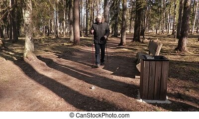 Man with hiking sticks collect and throw paper in waste...