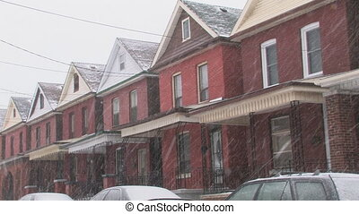 Snowy houses. Wide shot. - Row of old brick houses in a...