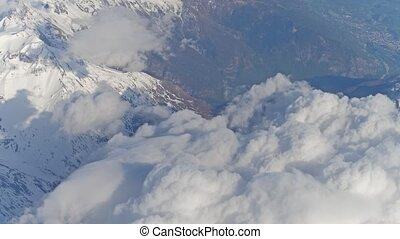 The Alps snowy mountain peaks and white clouds, aeial view....