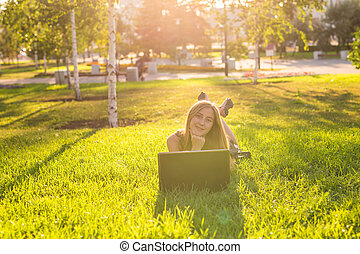 girl lying on the grass with laptop