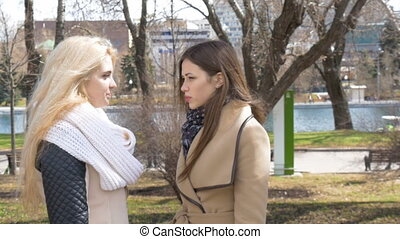 Meeting friends in the park. Two girls blonde and brunette...