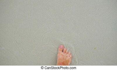a young girl walks along the shore of the beach. Feet closeup