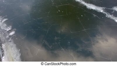 flying above frozen lake with cracked ice - aerial footage...