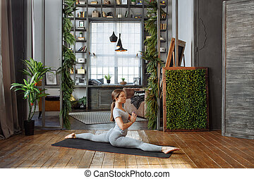 Young woman in homeware practicing balance yoga pose on...