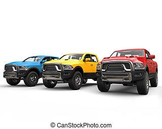 Red, blue and yellow modern pick-up trucks - studio shot