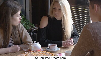 Two girls and a young man talking in a cafe sitting at a table. They drink tea and eat pizza. They tell the news, they smile. Close-up. Smooth motion of the camera.