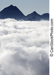 sea of clouds - pyramid-shaped peaks and sea of clouds in...