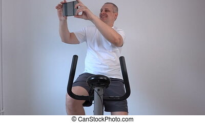 Man takes selfies on exercise bike