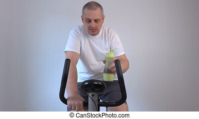 Man drinking from a bottle and used exercise bike