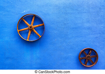 Blue Colonial Wall - Blue colonial wall with rusty wheels on...