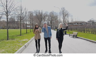 Young people are walking in the park. These are friends. The blonde does selfie, the brunette writes messages to the messenger, the young man talks loudly over the phone. Bright, sunny spring day.