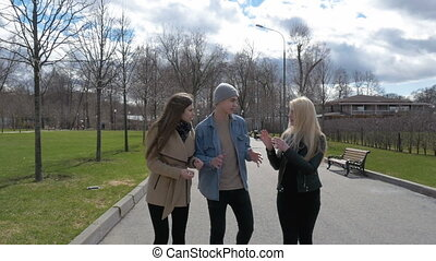 Young people walk in the park, tell the news, communicate,...