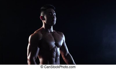 Asian bodybuilder demonstrates the inflated body, he is...
