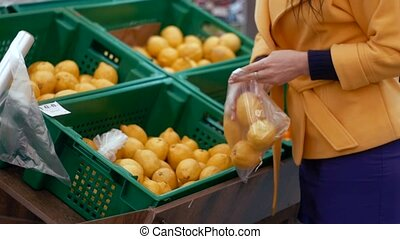 Woman selecting fresh lemon in grocery store produce department.