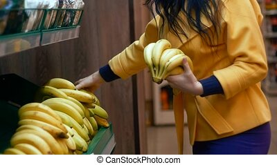 Woman selecting banana in grocery store produce department.