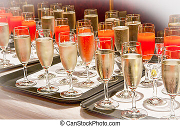 Row of glasses filled with champagne lined up ready to be...