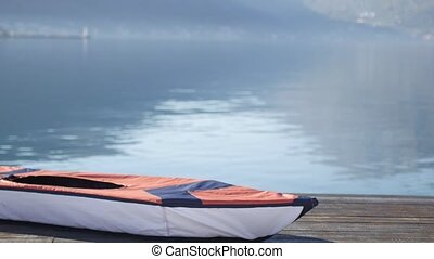 Kayak lies on the shore. Wooden jetty. Bay of Kotor in...