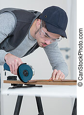 Tradesman using angle grinder to cut copper pipe