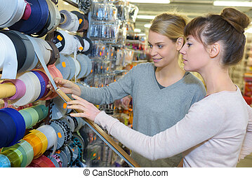 Shopkeeper measuring ribbon for customer