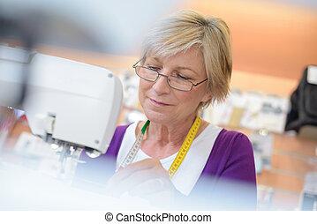 Mature woman using sewing machine