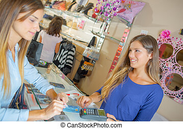 Lady paying for purchases by card in a clothes shop