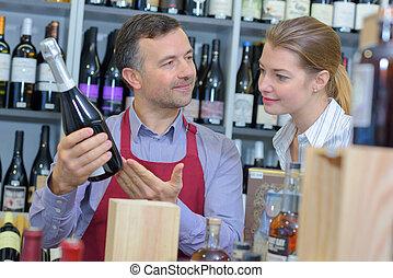 Wine merchant advising customer
