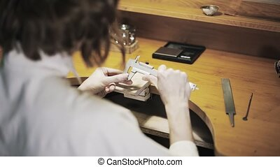 Rear view of woman jeweller measuring a ring