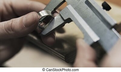 Close up of woman jeweller measuring a ring