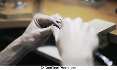 Woman jeweller polishing a ring - Rear view of a woman...