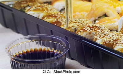 Chopsticks Taking Sushi Roll and Dip into Soy Sauce. Variety...